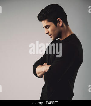 Side view of young man standing with arms crossed looking down. Hispanic male model on grey background. - Stock Photo