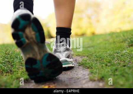 Feet of a runner in park. Woman walking in the park, close up of feet. Fitness and exercising training. - Stock Photo