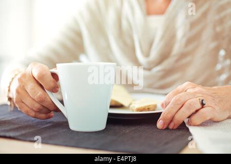 Closeup of a senior woman's hands with a cup of coffee - Stock Photo