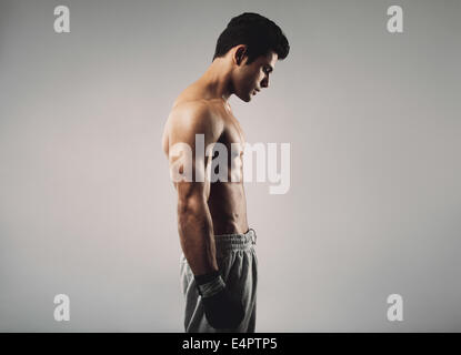 Side view of fit young man wearing boxing gloves looking down on grey background - Stock Photo