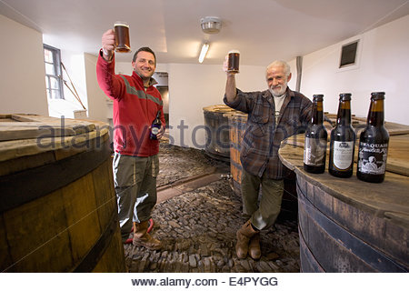 Two brewers raise a glass in the tun room at the original brewhouse at Traquair House Brewery, Traquair House, near - Stock Photo