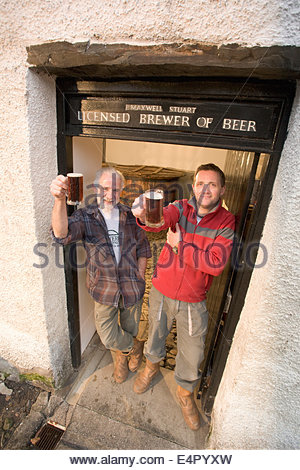 Two brewers raise a glass in the doorway to the tun room at the original brewhouse at Traquair House Brewery, Traquair - Stock Photo