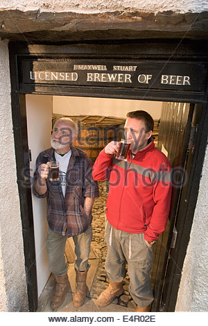 Two brewers sample a beer in the doorway to the tun room at the original brewhouse at Traquair House Brewery, Traquair - Stock Photo