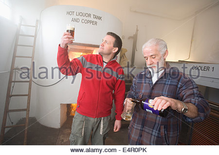 Two brewers check the quality of the finished product by the Hot Liquor Tank at the original brewhouse at Traquair - Stock Photo