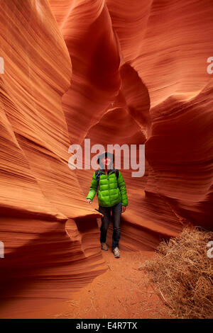 Tourist, tumbleweed, and eroded sandstone formations in Rattlesnake Canyon, near Page, Navajo Nation, Arizona, USA - Stock Photo