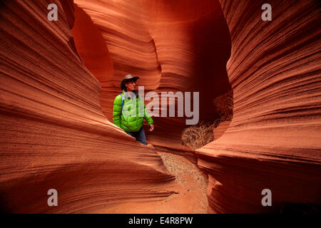 Tourist and eroded sandstone formations in Rattlesnake Canyon, near Page, Navajo Nation, Arizona, USA - Stock Photo