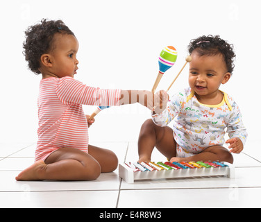 Twin boy and girl (18 months) playing with xylophones and maracas - Stock Photo