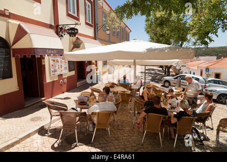 People sitting drinking outdoors at a cafe, Silves, Algarve, Portugal Europe - Stock Photo