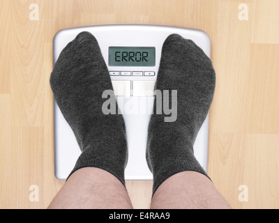 overweight man on personal scales - Stock Photo