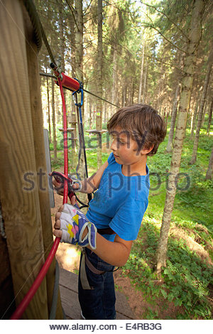 A youngster enjoys a tree top adventure course, West Lothian, Scotland. - Stock Photo