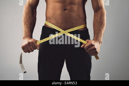 Fitness man measuring his body. Cropped and mid-section image of young man measuring his waist with tape measure - Stock Photo