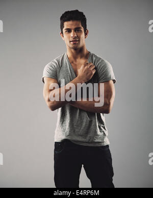 Portrait of handsome young man posing confidently. Hispanic male fashion model against grey background. - Stock Photo