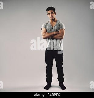 Full length portrait of muscular young man standing with his arms crossed. Hispanic mate model in casuals with copy space.