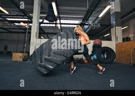 Fit female athlete working out with a huge tire, turning and flipping in the gym. Crossfit woman exercising with - Stock Photo