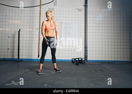 Fitness woman working out with a medicine ball. Strong young caucasian woman doing crossfit workout at gym. - Stock Photo