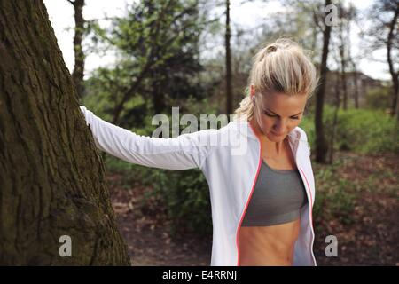 Beautiful young woman resting by a tree after jogging in a park. Fit female athlete taking a break after running. - Stock Photo