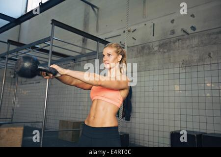 Fitness woman swinging kettle bell at gym. Young caucasian woman doing swing exercise with a kettlebell as a routine - Stock Photo