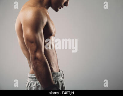 Cropped image of muscular young man torso on grey background with copy space. - Stock Photo