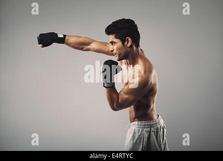 Profile view of young man practicing shadowboxing on grey background. Muscular young male model working out. - Stock Photo