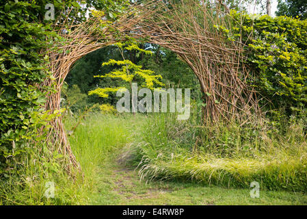 Willow Archway dividing a hedge over garden path at RHS Harlow Carr. Harrogate, England - Stock Photo