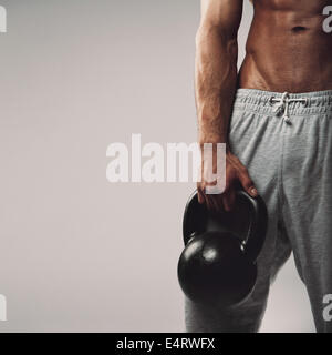 Close up image of young man's hand holding kettlebell. Crossfit workout concept with copyspace on grey background. - Stock Photo