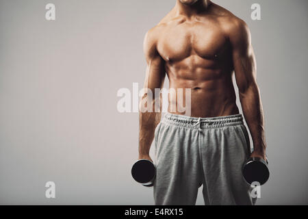 Studio shot of a male model in sweatpants holding dumbbells in both hands on grey background with copy space. Shirtless - Stock Photo