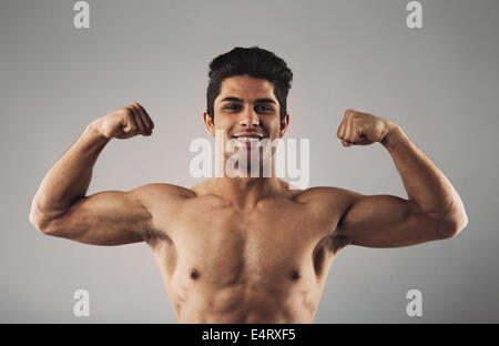 Portrait of hispanic young muscular man flexing his biceps isolated on grey background. Happy masculine man pulling - Stock Photo