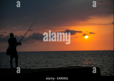 Man silhouette at sunset fishing in Cuba - Stock Photo