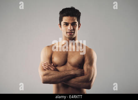 Portrait of a bare-chested muscular man standing with his arms crossed. Fit and masculine young hispanic man shirtless - Stock Photo