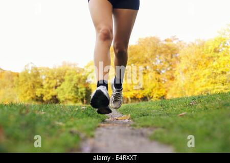 Close-up of feet of a runner running in park. Woman training for fitness. Female legs jogging in park - Outdoors - Stock Photo