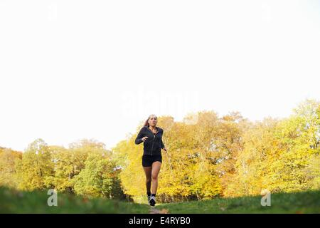 Image of fitness woman running in autumn park outdoors. Female athlete jogging in park. Caucasian female fitness - Stock Photo