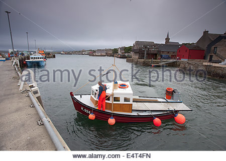 A small fishing boat returns to the harbour at Stromness, Mainland, Orkney, Scotland. Stock Photo