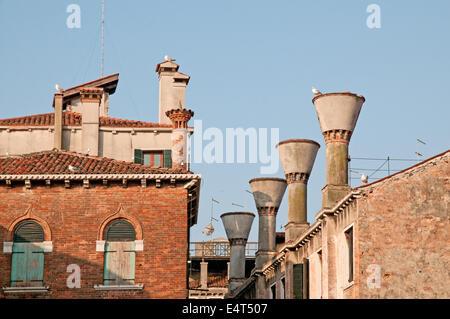 Chimney pots on houses near Rialto Market Venice Italy with TV television aerials and Lesser Black Backed Gulls - Stock Photo