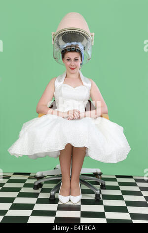Woman in 1950s style wedding dress sitting under a vintage salon hair drier - Stock Photo