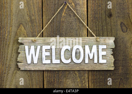 Rustic wood welcome sign hanging on wooden door - Stock Photo