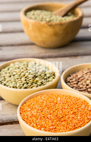 Dried orange lentils in the clay dish. Other types of lentils in the background - Stock Photo