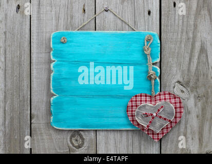 Blank antique blue sign with plaid and wood hearts hanging on wooden door - Stock Photo