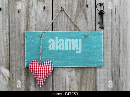 Blank antique blue sign with red checkered heart and iron keys hanging on wooden door - Stock Photo