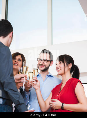 Mature businesswoman toasting group of young business people with glasses of champagne, Germany - Stock Photo