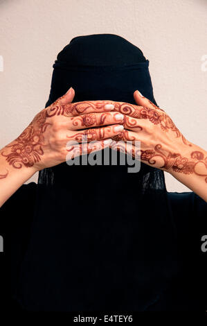 Portrait of woman in black muslim hijab and muslim dress, hands covering eyes and painted with henna in arabic style - Stock Photo