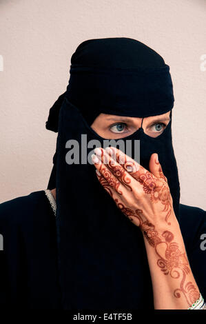 Portrait of woman in black muslim hijab and muslim dress, hand covering mouth, hands painted with henna in arabic - Stock Photo
