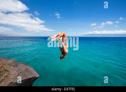 Woman doing backflip off cliff into the ocean. Summer fun lifestyle. - Stock Photo