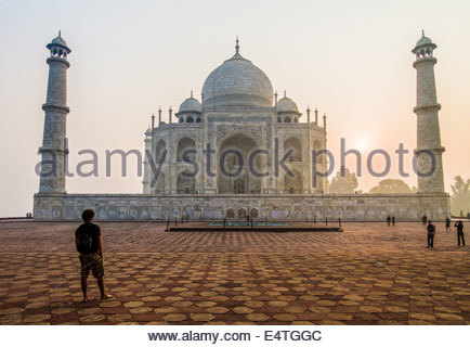 A Man Stands Before The Taj Mahal As The Sun Comes Up Behind It, Agra, India, Asia - Stock Photo