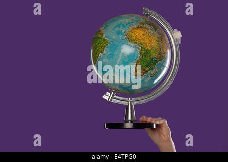 Female hand with a globe - Stock Photo