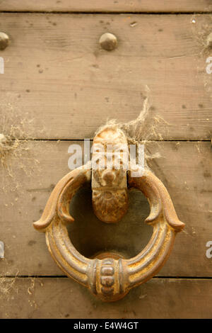 Old metal doorknocker on wooden door, Bergamo, Italy. - Stock Photo