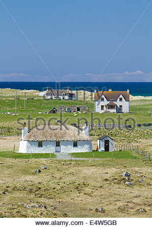 Howmore, with a traditional thatched croft in the foreground, Isle of South Uist, Outer Hebrides, Scotland. - Stock Photo
