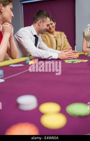 Happy people placing bets at poker game - Stock Photo
