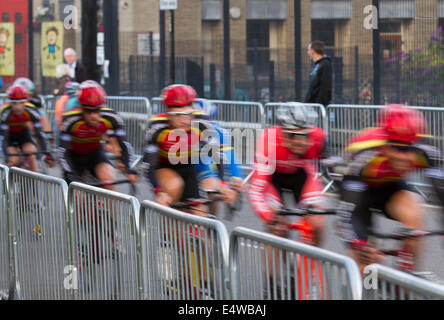 Fast moving road cyclists blurred riders at Colne, Lancashire, UK 16th July, 2014. Street racing at the Colne Grand - Stock Photo