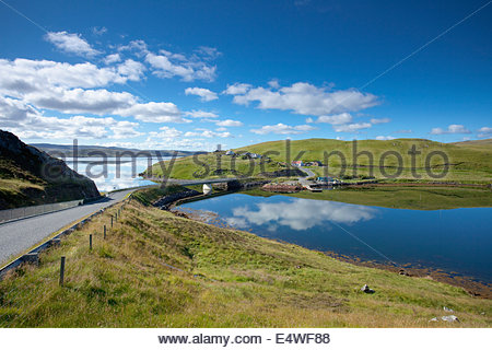 The view down the single track road to the bridge across to the small island of Muckle Roe from Mainland, Shetland, - Stock Photo