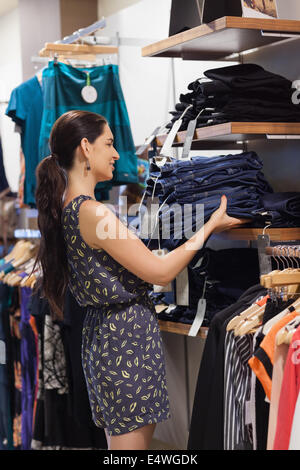 Woman putting jeans on shelf - Stock Photo